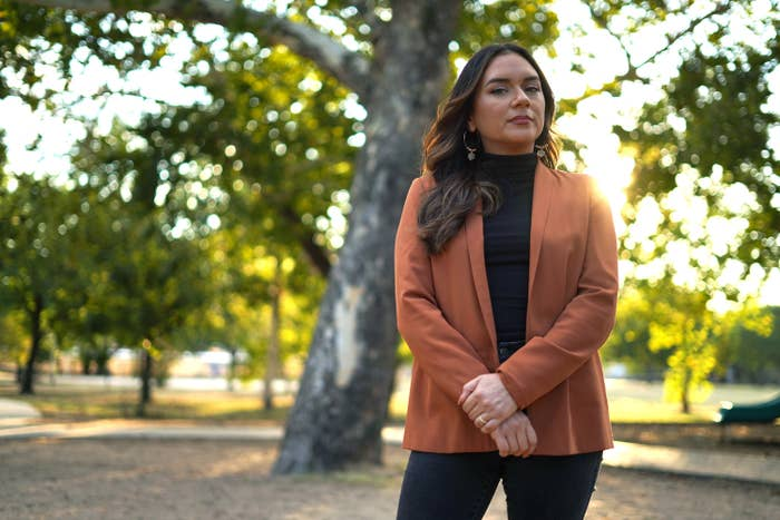 A woman in a blazer stands in front of a tree in the park, arms crossed and looking at the camera