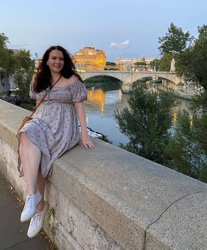 writer sitting on edge of bridge with Rome in the background