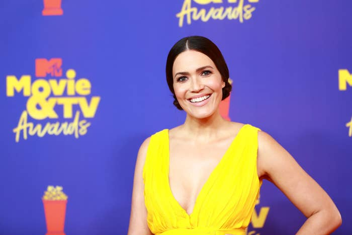 Mandy Moore smiling in a deep-V top on the red carpet