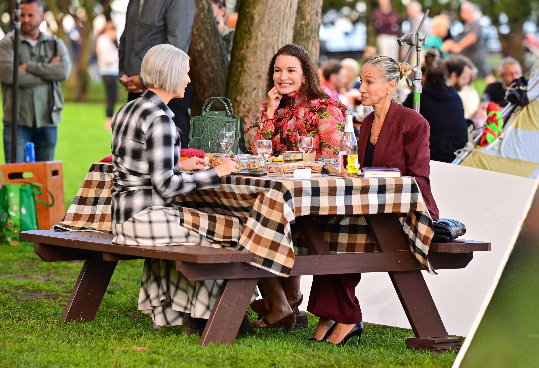 Cynthia Nixon, Kristin Davis, and Sarah Jessica Parker sitting at a table outdoors