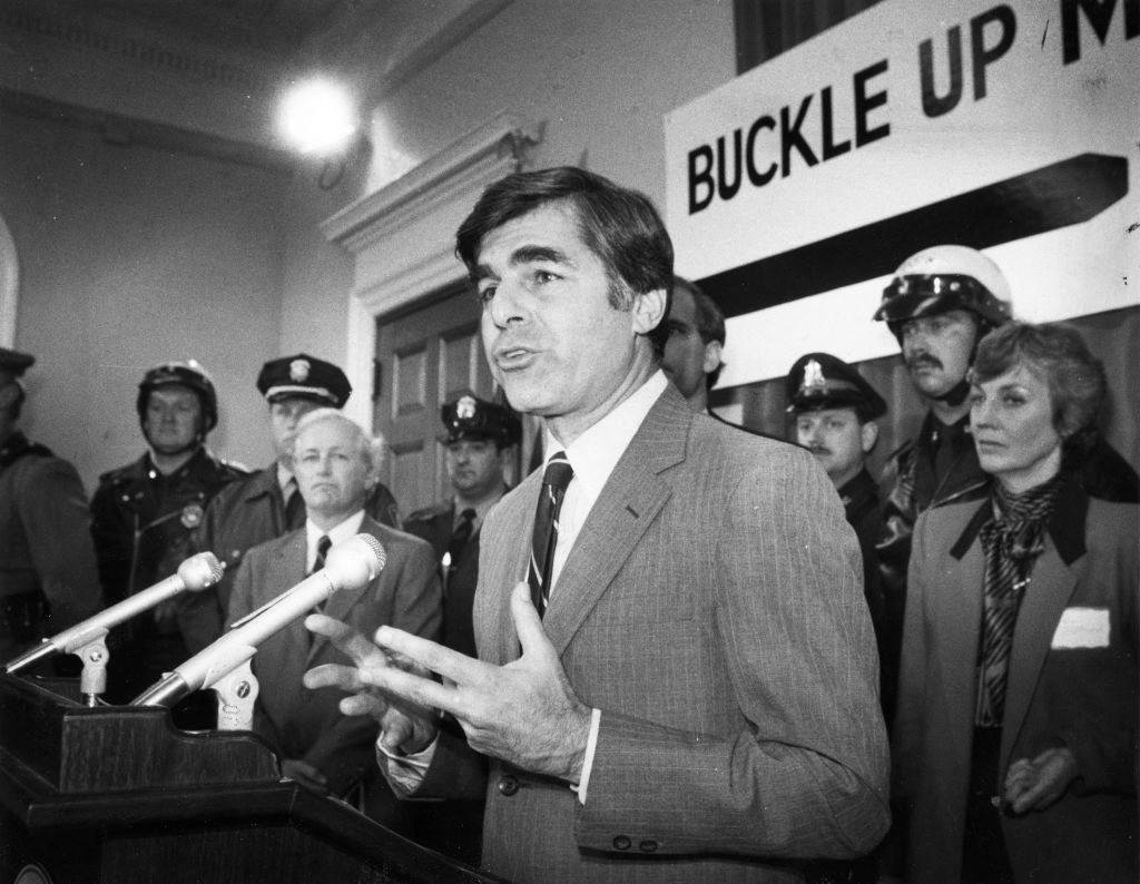 A man speaking at a podium with law enforcement behind him with a sign that says Buckle Up