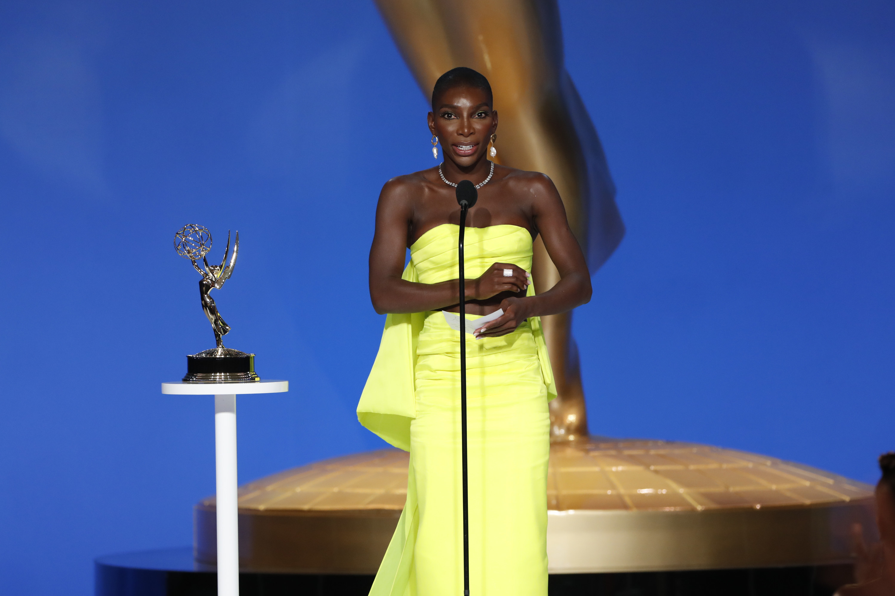 Michaela standing in front of a microphone in a gown