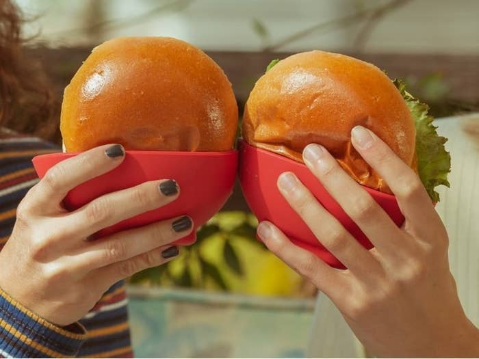 two people holding hamburgers that are placed in the silicone holders