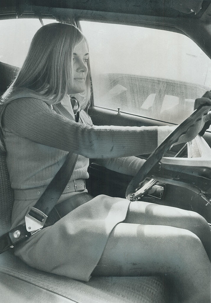 An old photo of a woman driving with her seatbelt on