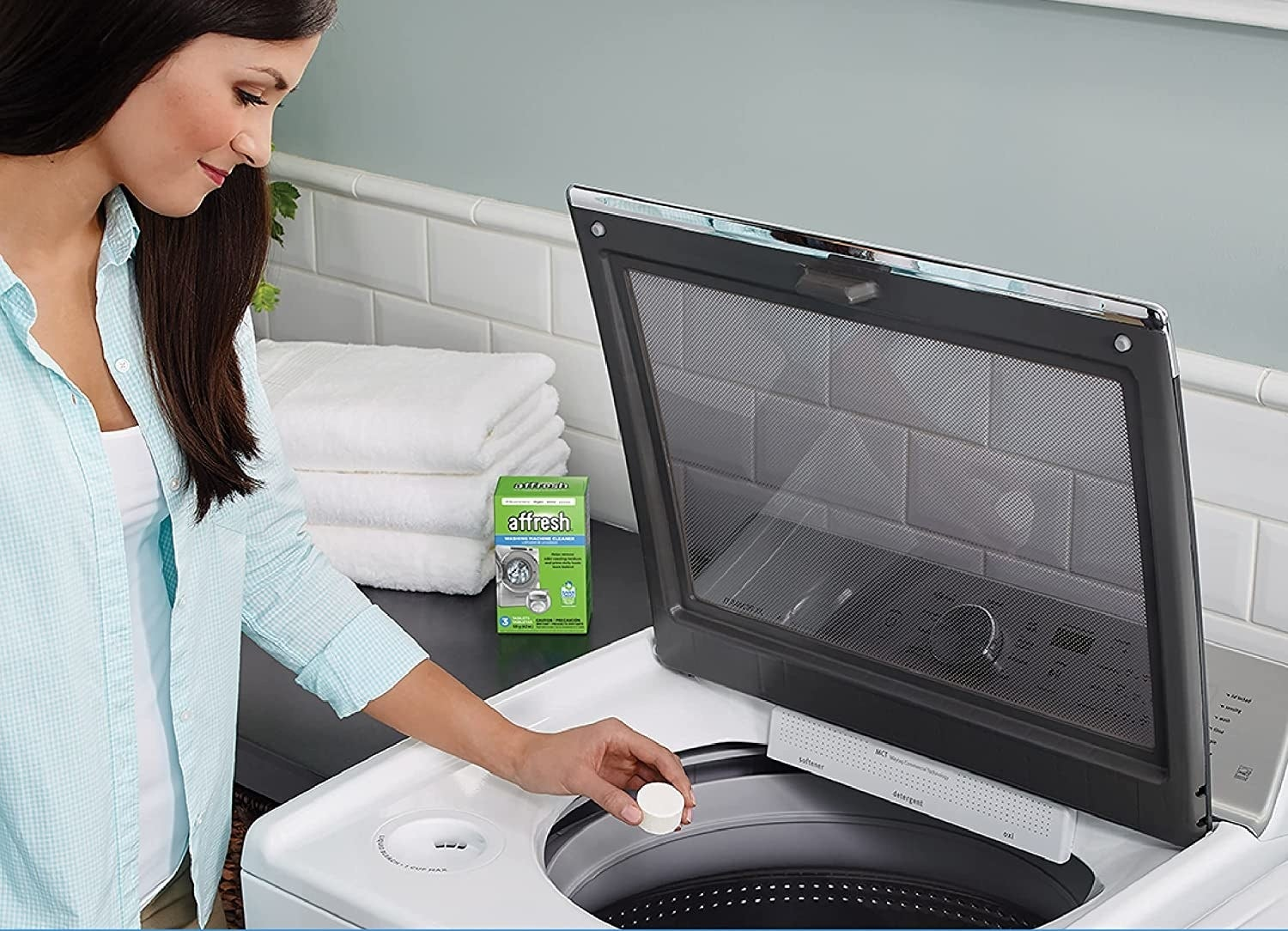 a model putting the tab in a top-loading washer