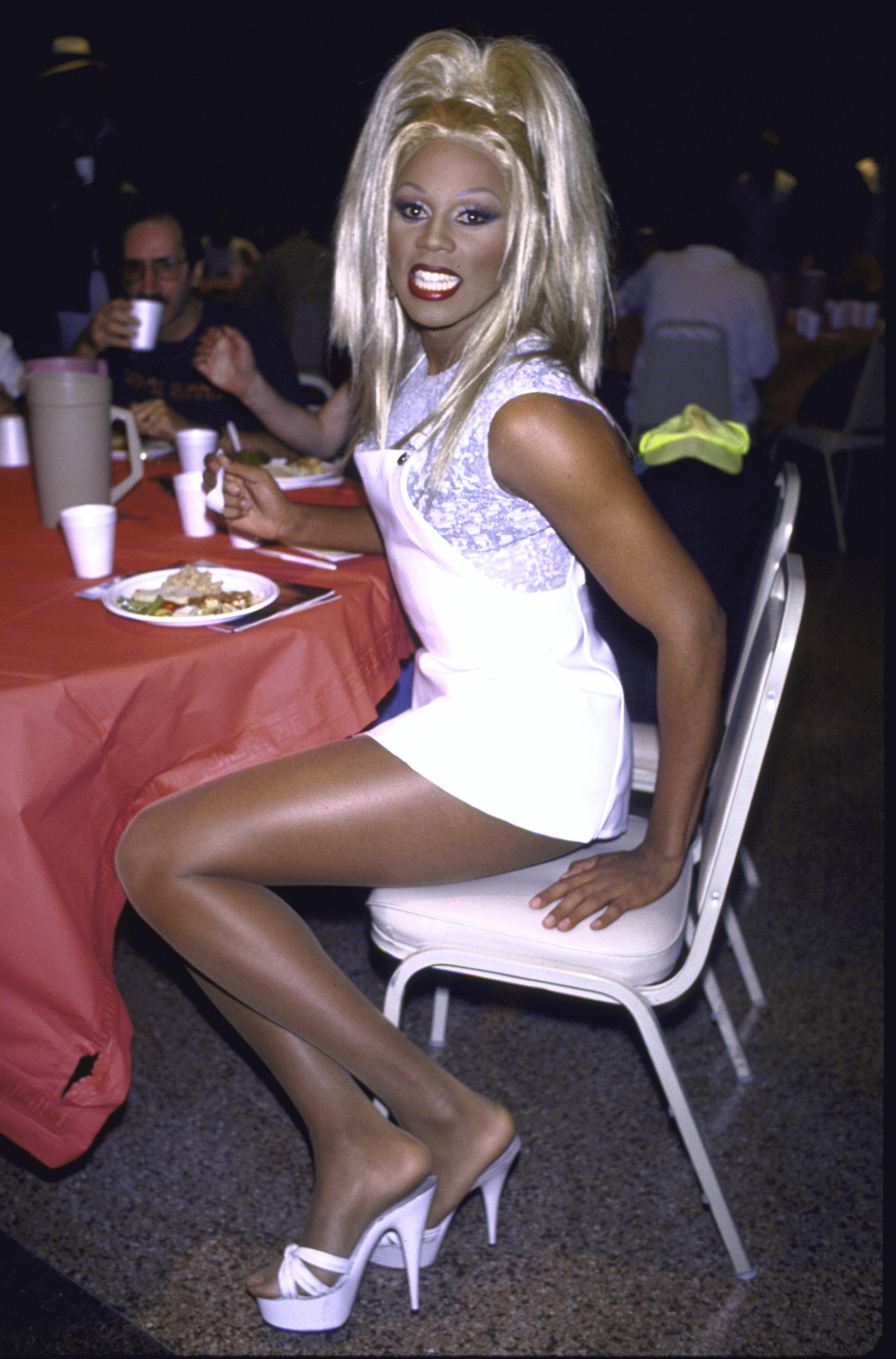 A young RuPaul posing for a photo as she eats at an event