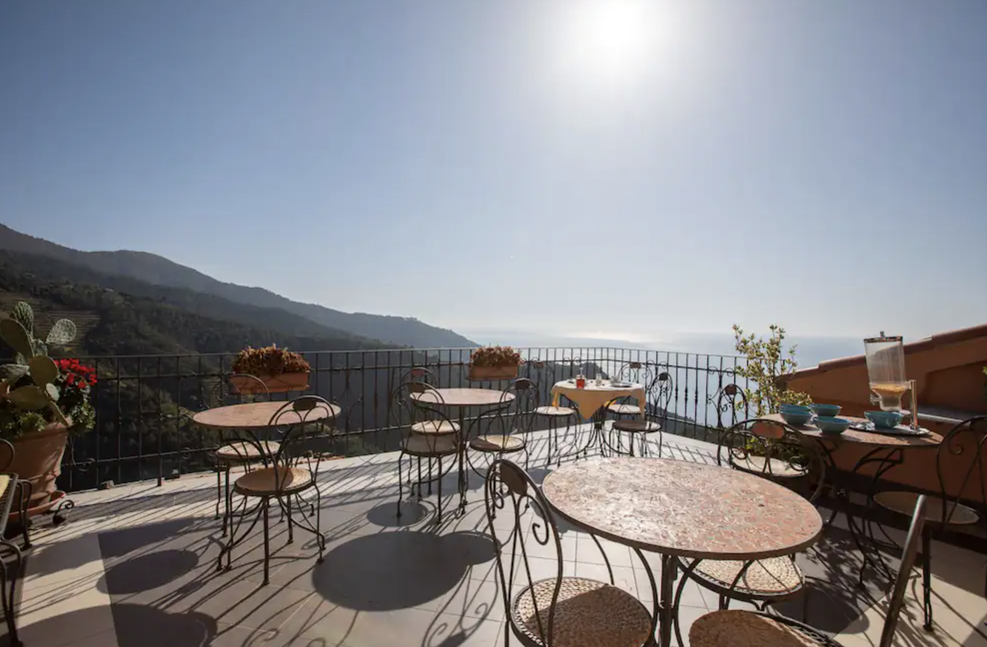 Outdoor terrace with breakfast tables overlooking the mountains and sea.