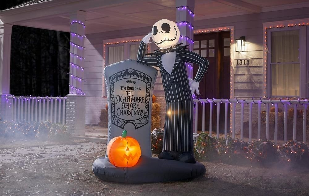 a blow up of jack skellington leaning next to a tomb stone