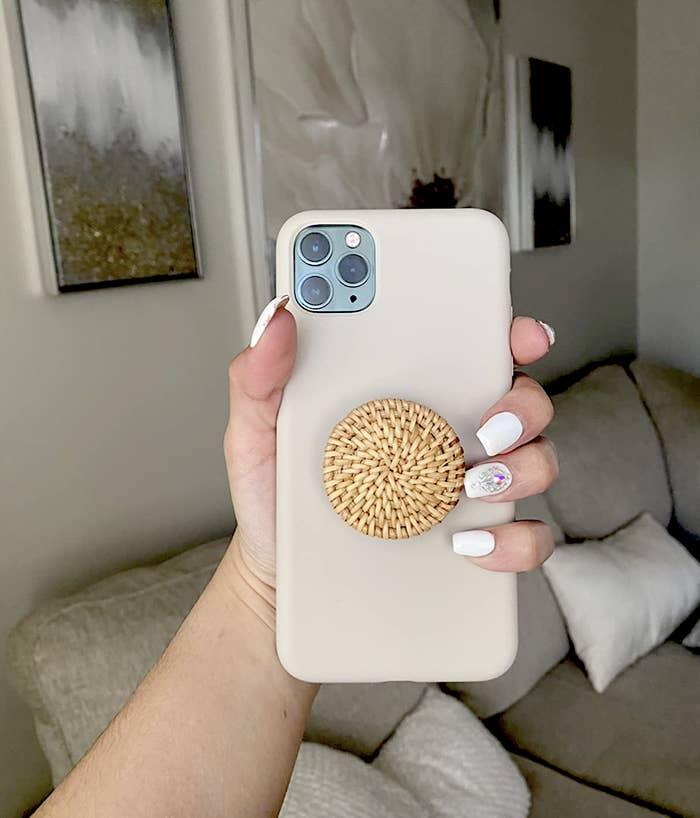 reviewer holding phone with the rattan phone grip attached to the back