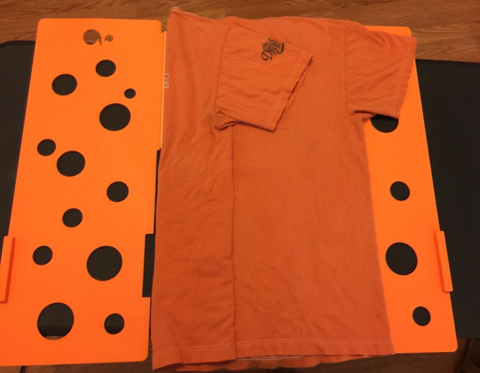 a review photo of an orange shirt being folded on the orange board