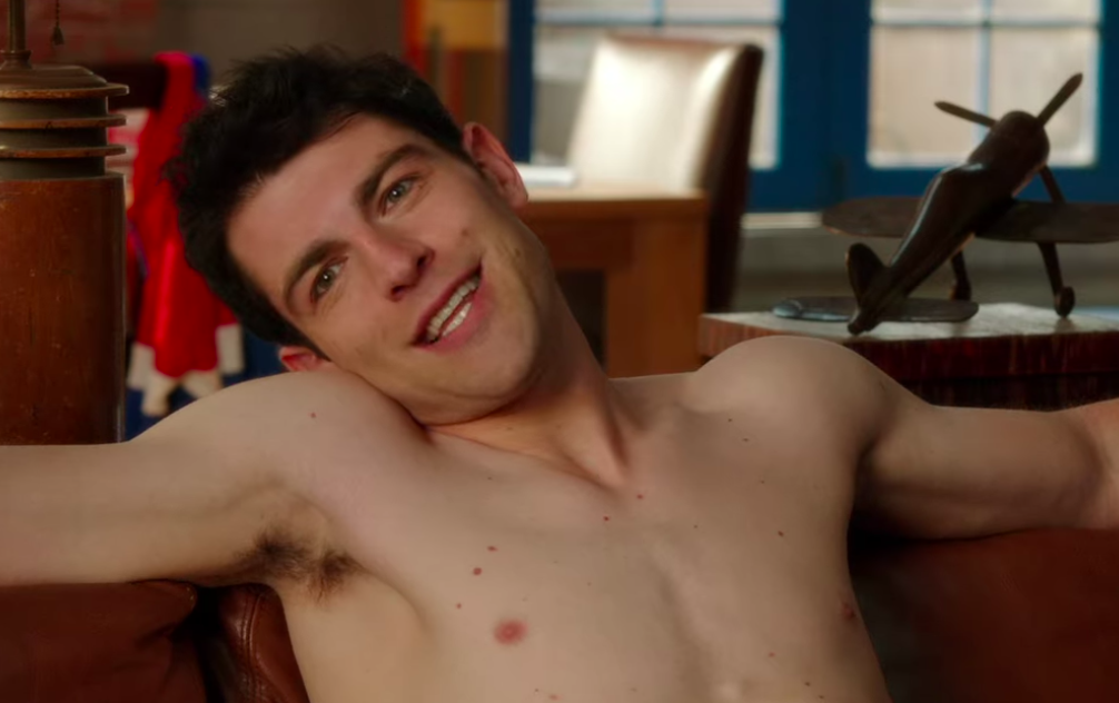 Schmidt sits on a couch shirtless