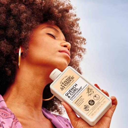 model with curly hair holds the bottle