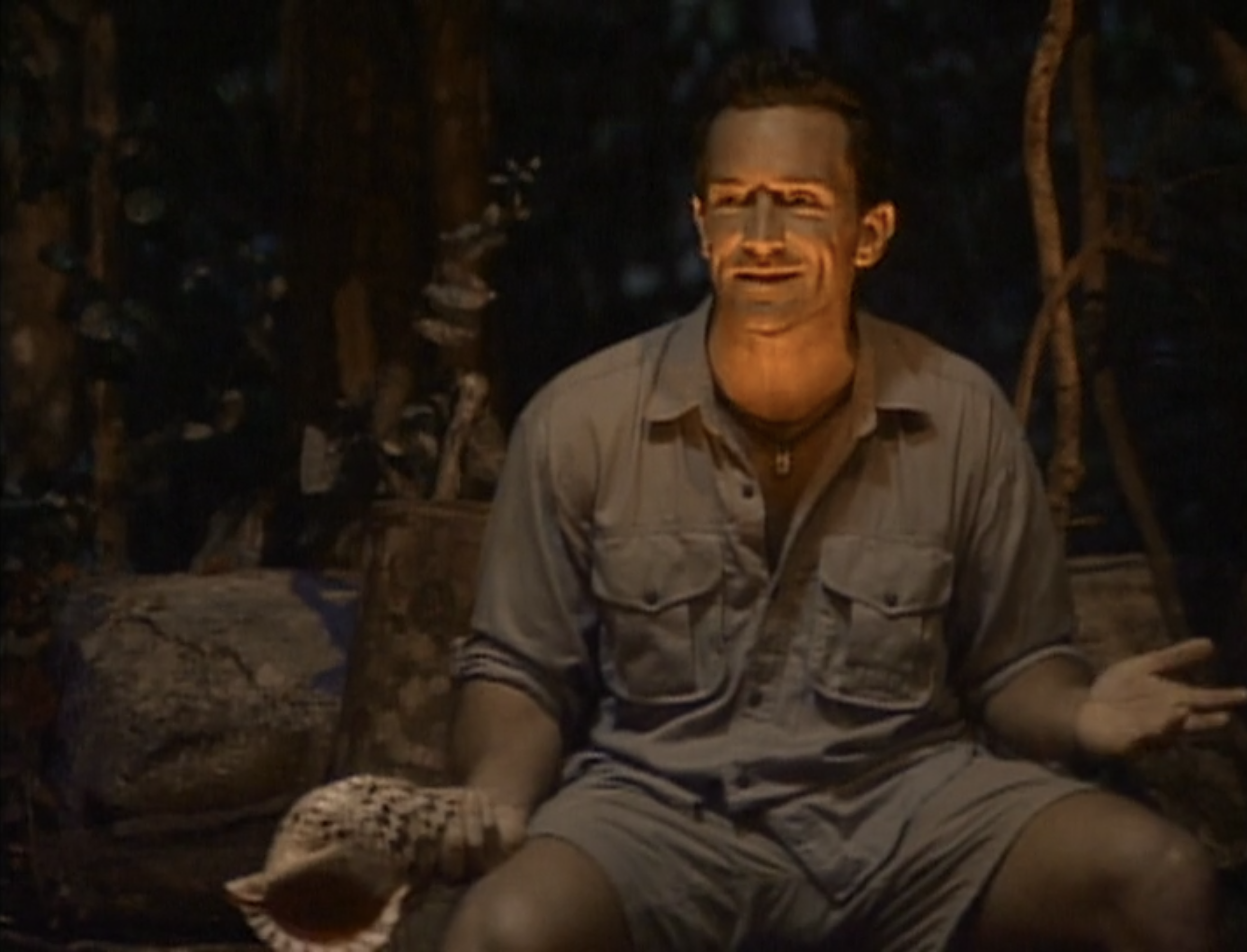 Jeff Probst holding a conch shell at Tribal Council