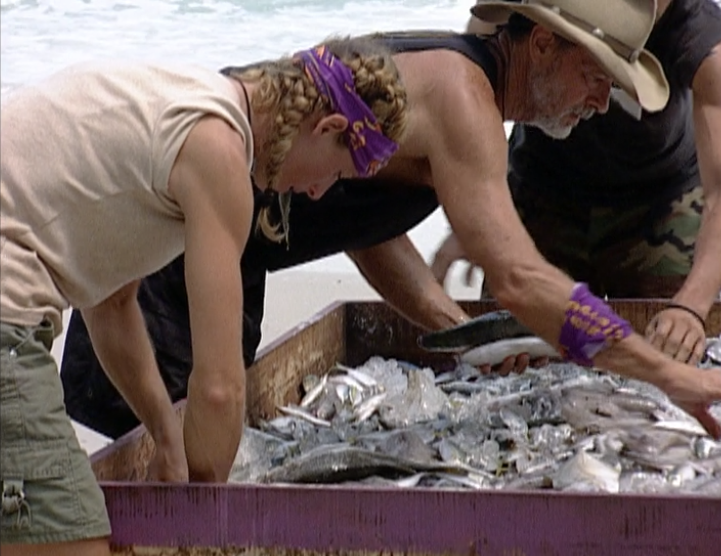 A tribe sorts through a large pallet of fish on Survivor: Thailand