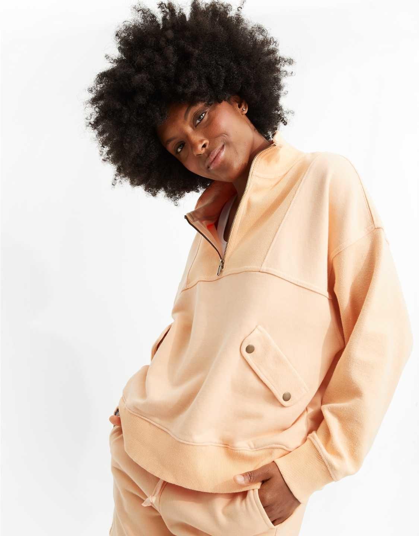 a model in a peach colored half zip sweatshirt