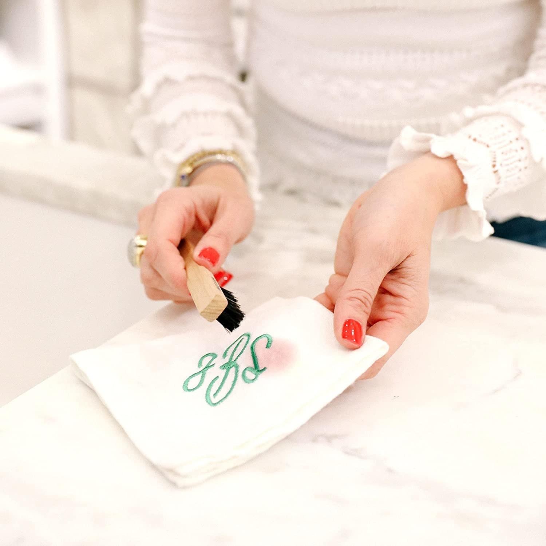 a model using the brush to scrub a handkerchief
