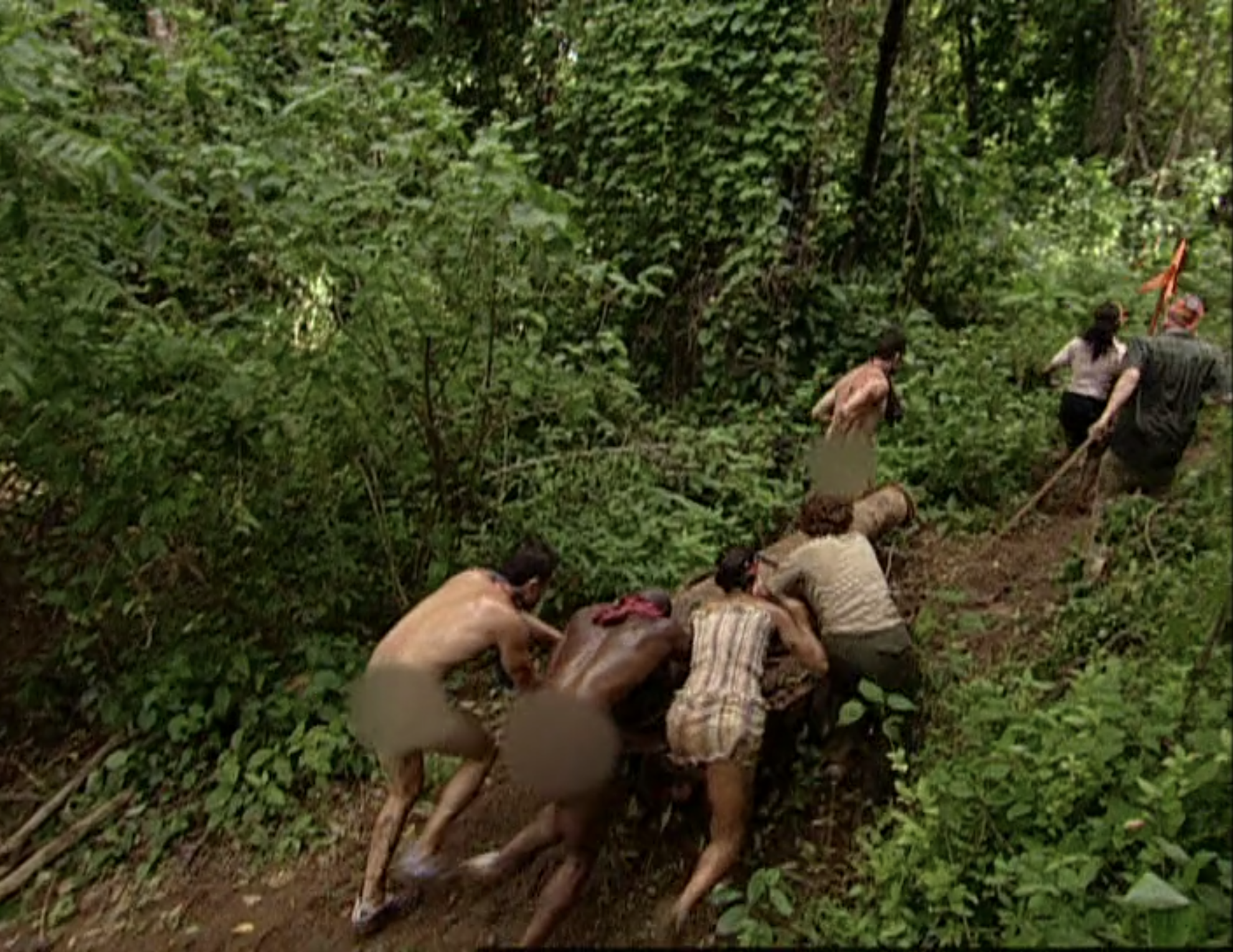 A tribe including three naked men push a cannon through the forest on Survivor: Pearl Islands