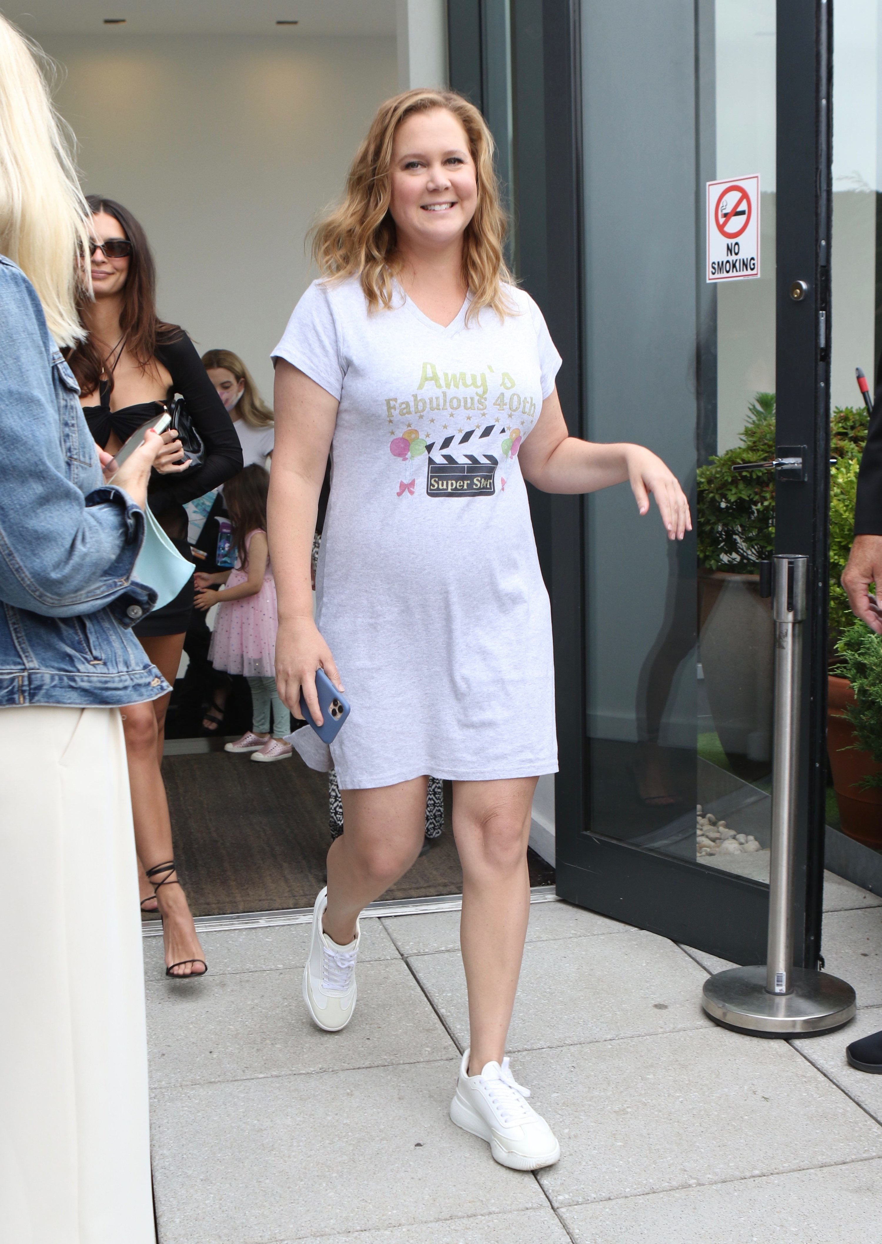 Amy Schumer walks through a doorway with Emily Ratajowski right behind her