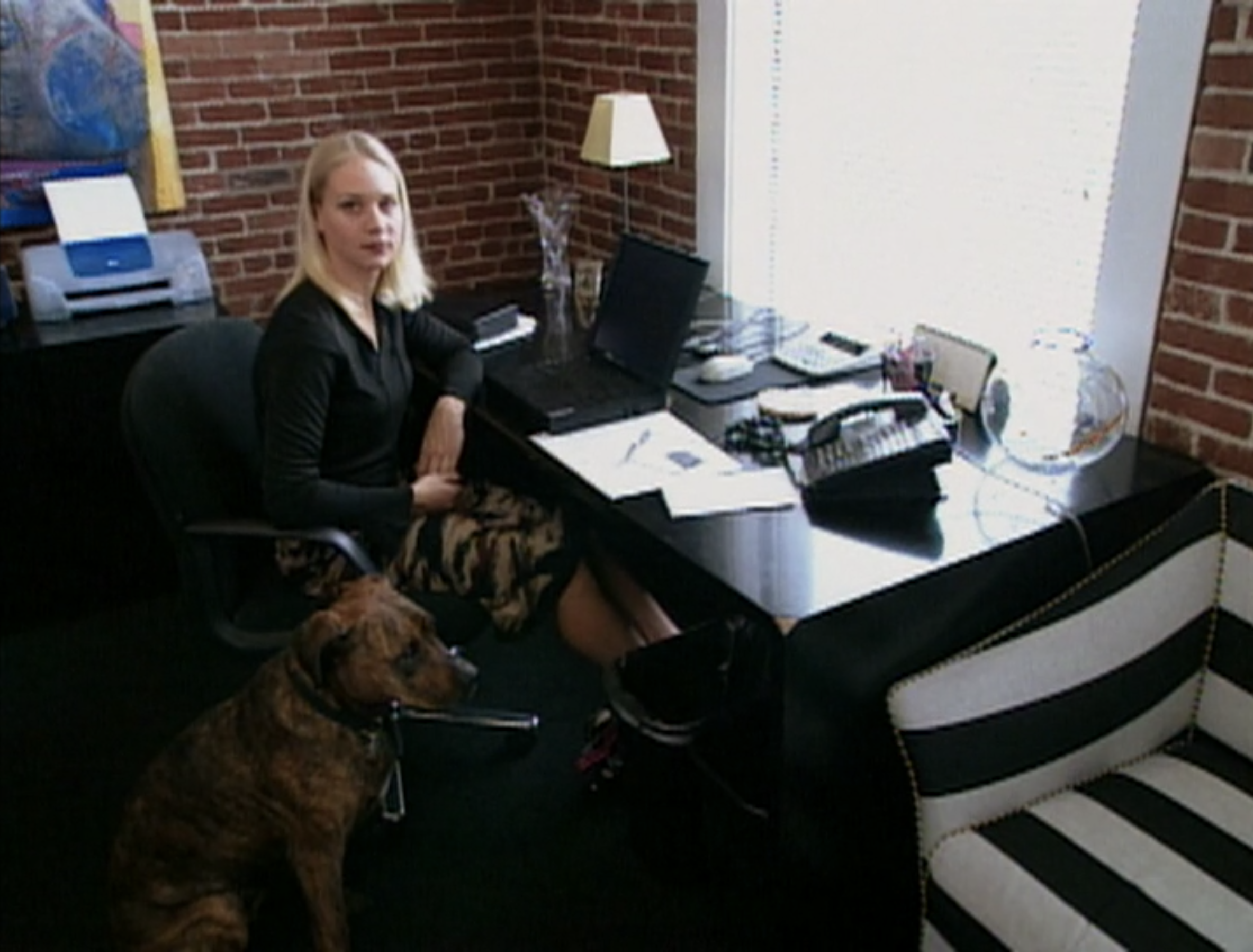 Lindsey Richter sits in an office with her dog on Survivor: Africa