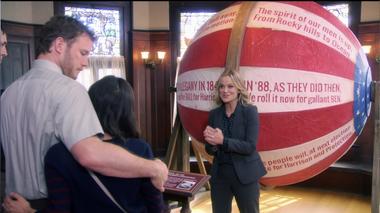Leslie Knope speaking in front of the giant ball