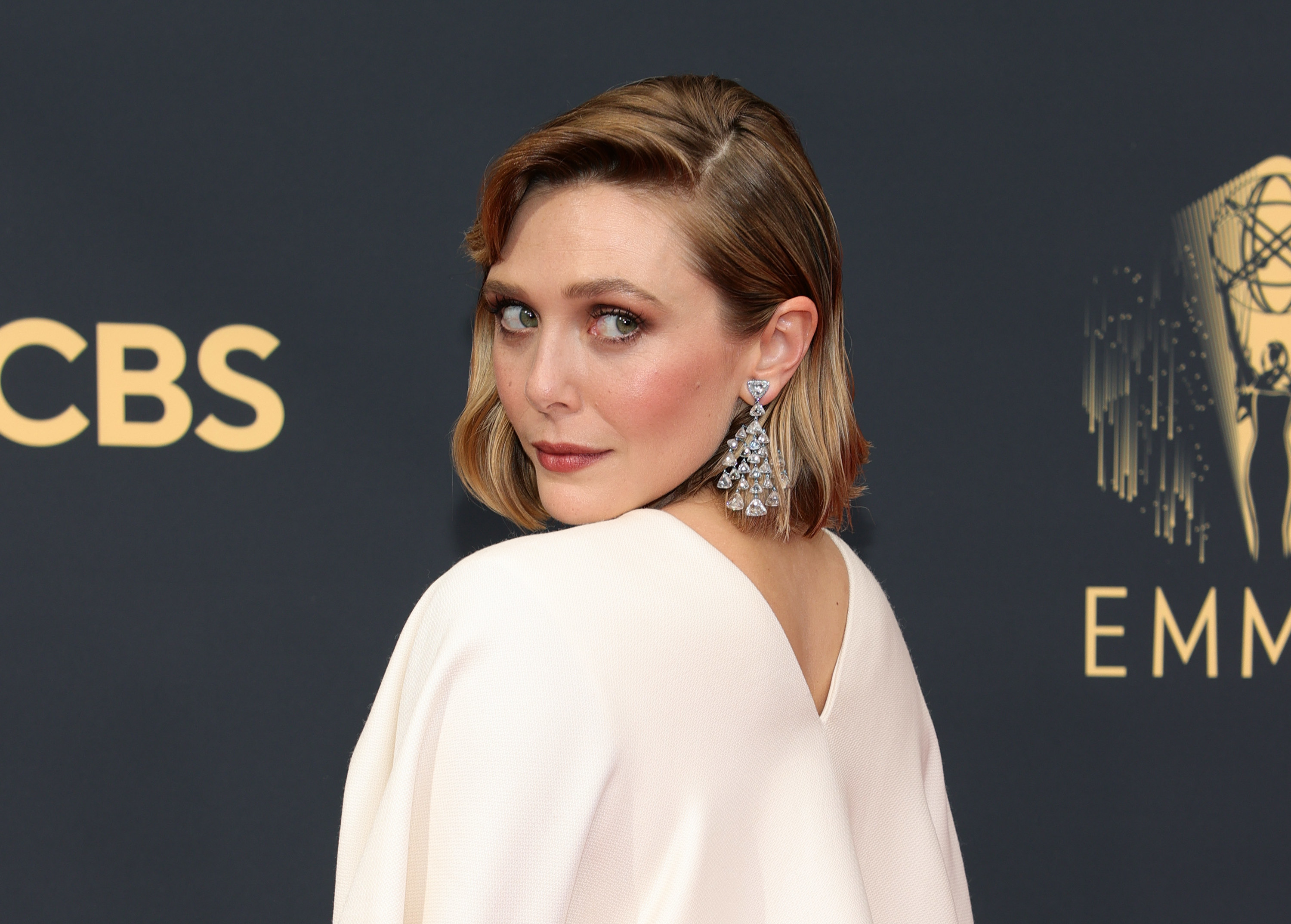 Elizabeth Olsen in a white gown with long diamond earrings at the 2021 Emmys