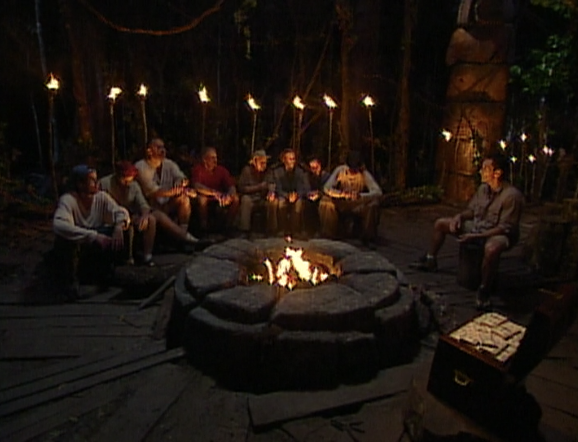 The tribe sits at Tribal Council across from a large chest of money in Survivor: Borneo