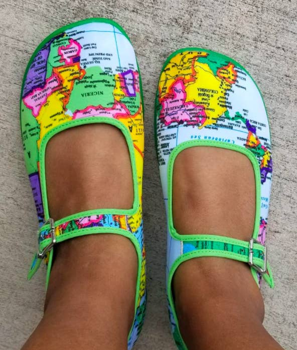 reviewer's feet in the Mary Janes with a colorful world map print all over it and bright green trim
