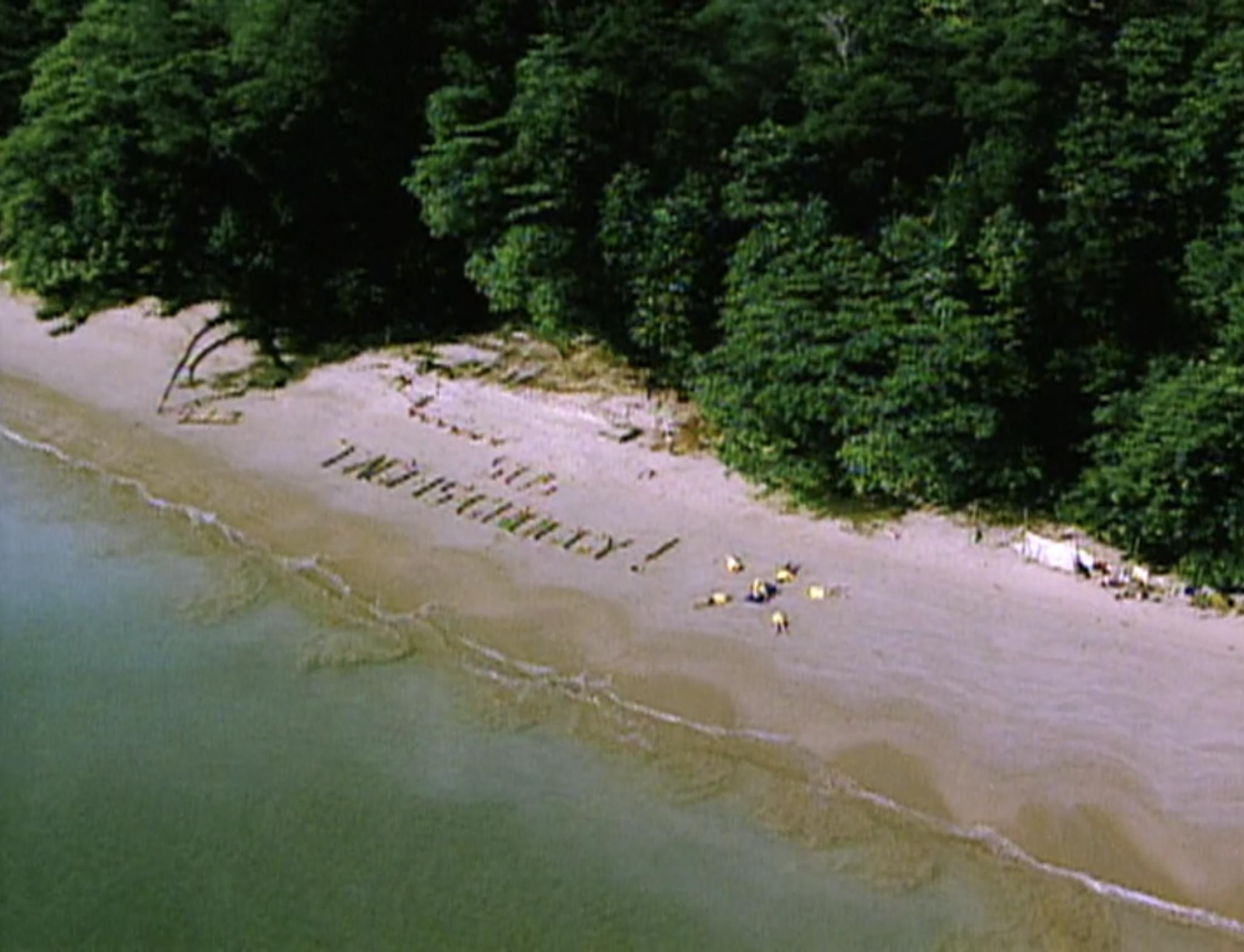 """A beach with a sign reading """"SOS Tagi is Groggy"""" on Survivor: Borneo"""