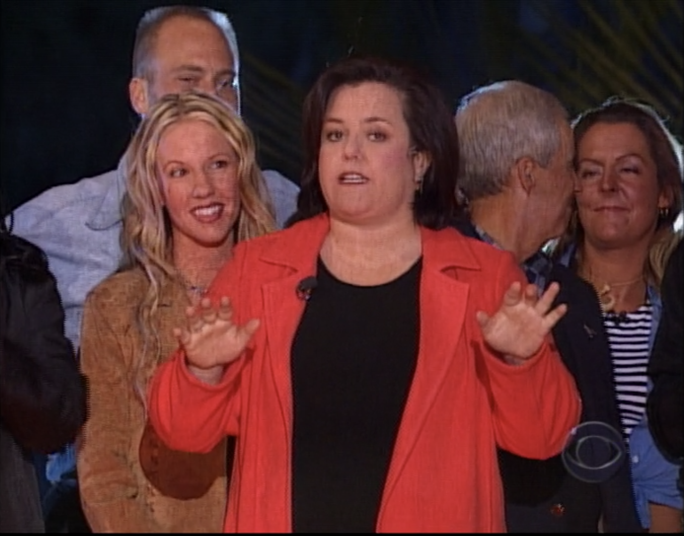 Rosie O'Donnell stands in front of castaways at the Survivor: Marquesas reunion