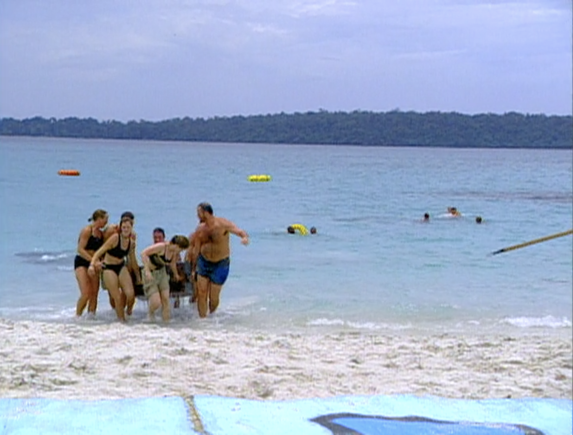 A tribe carries a large crate out of the water in an immunity challenge in Survivor: Borneo