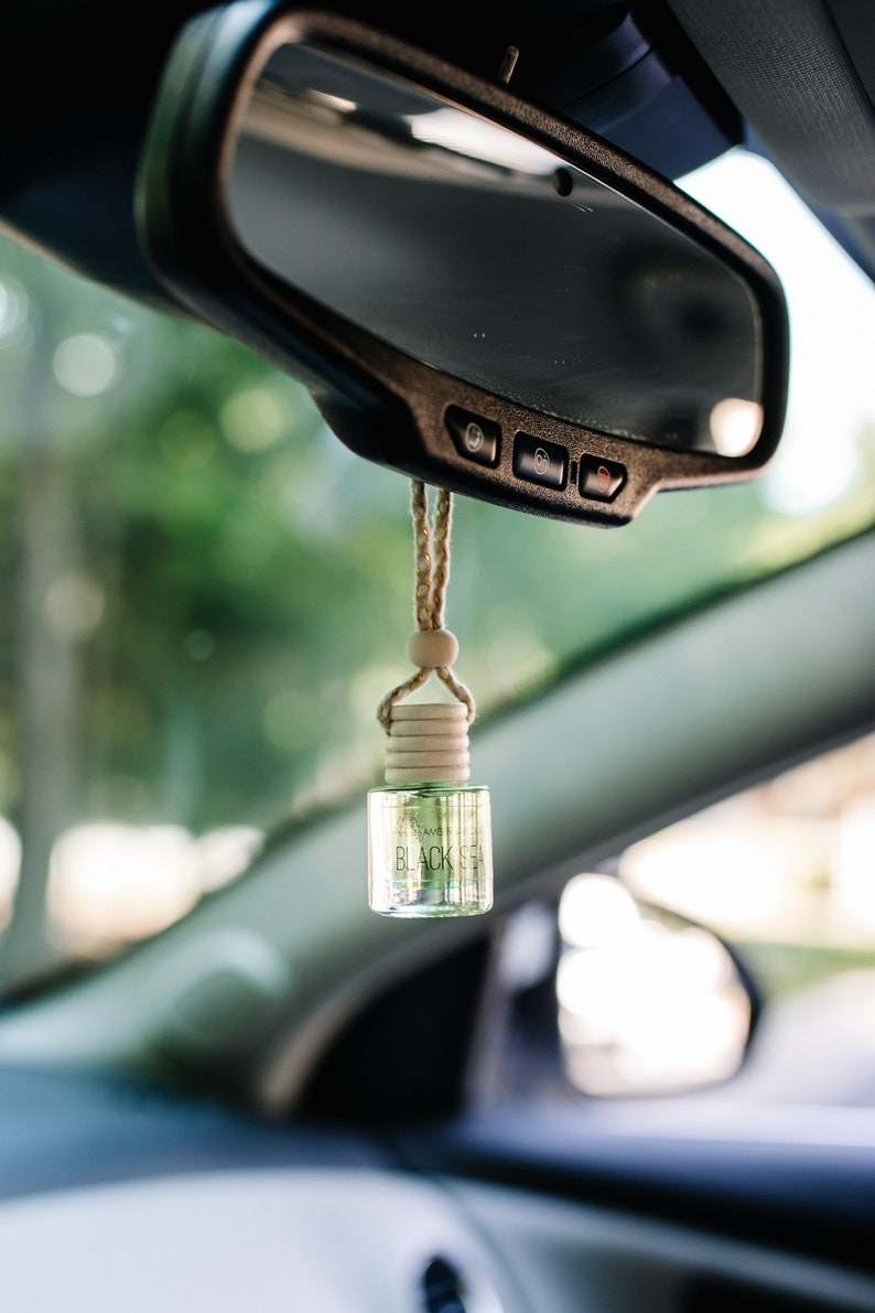 the car diffuser hanging from the rearview mirror of a car