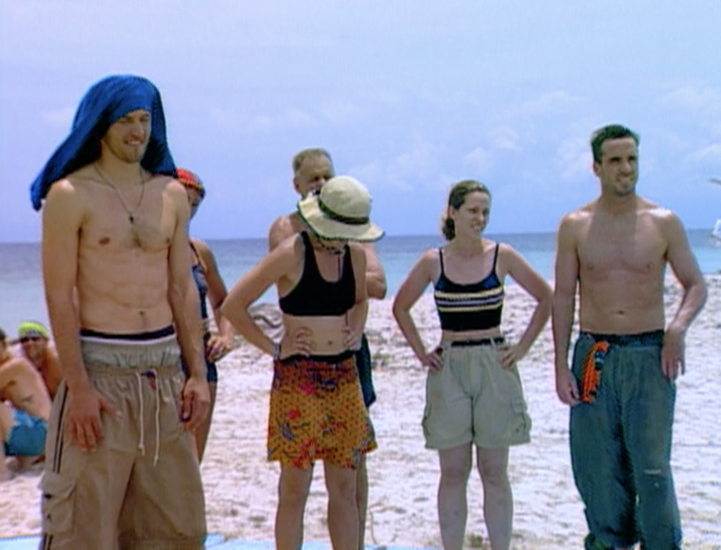 Contestants stand in a chaotic formation blocking each other on the beach on Survivor: Borneo