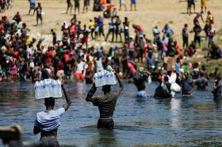 Two people carrying cases of water on their head cross back over the river to a crowd of people waiting