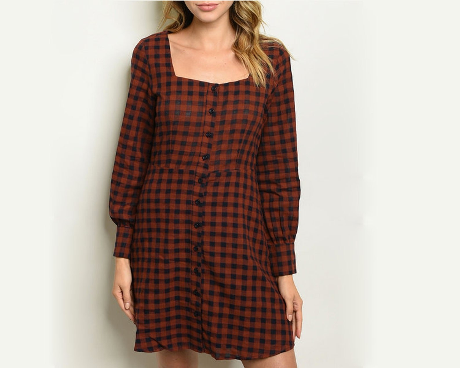 model in long sleeve brown and black gingham dress