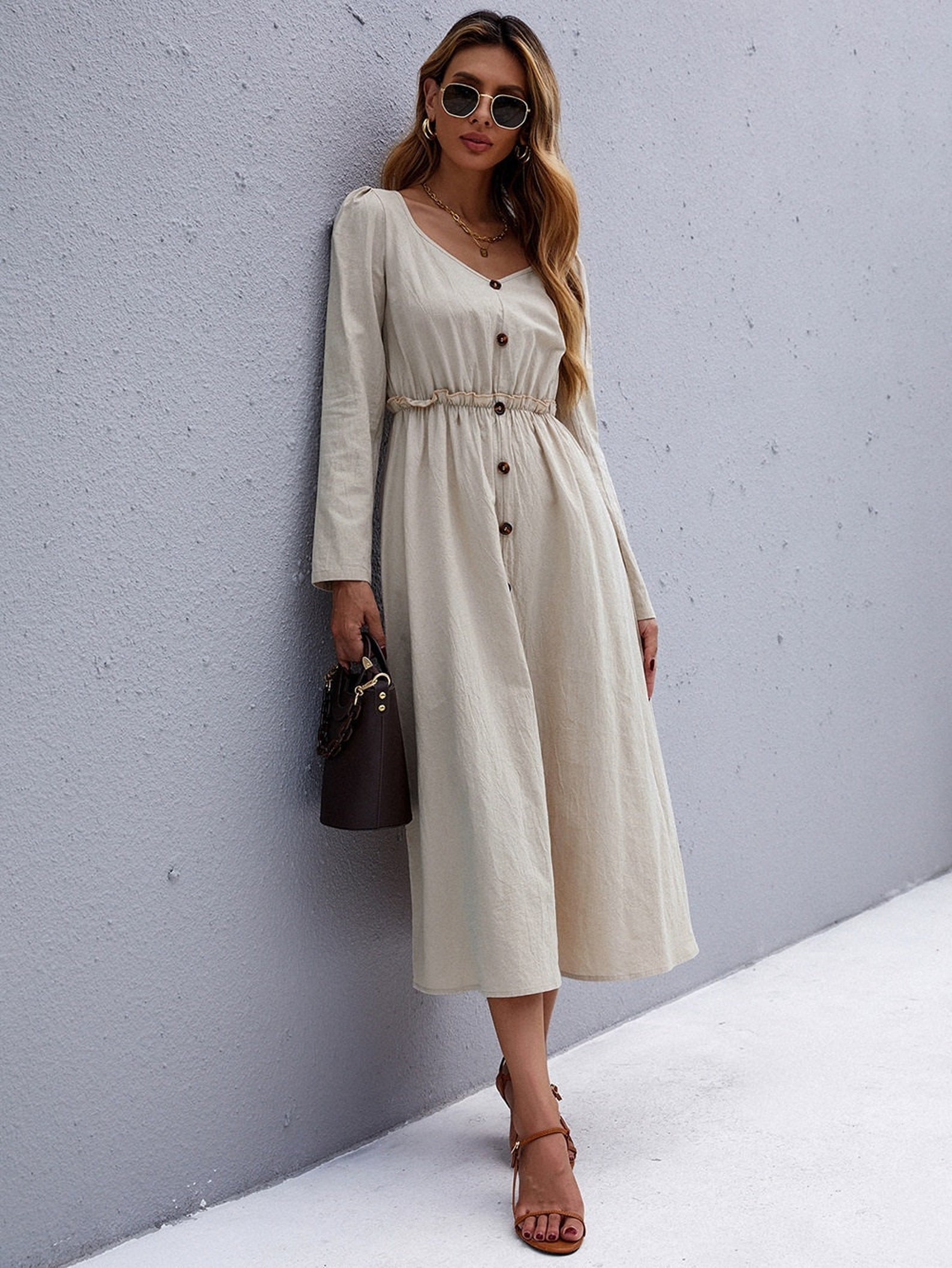 model wearing long sleeve midi dress in khaki with buttons down the front