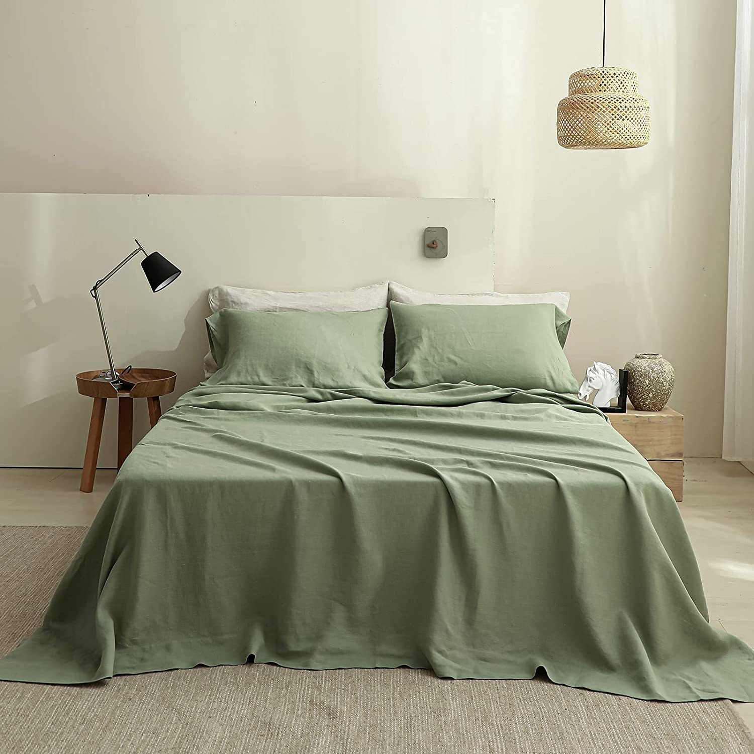 olive green sheets on loosely made bed