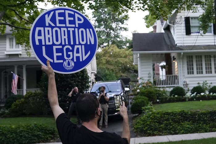 """A protester standing in a street holds up a sign that reads """"Keep abortion legal"""""""