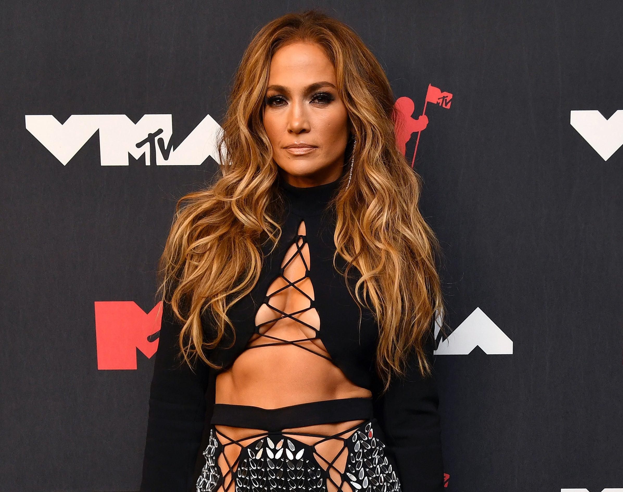 Jennifer looks serious in a crop top with cut out strings in the middle