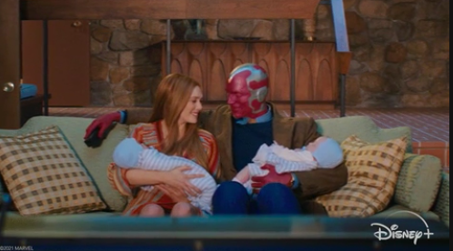 Wanda and Vision holding their twin baby boys on their couch