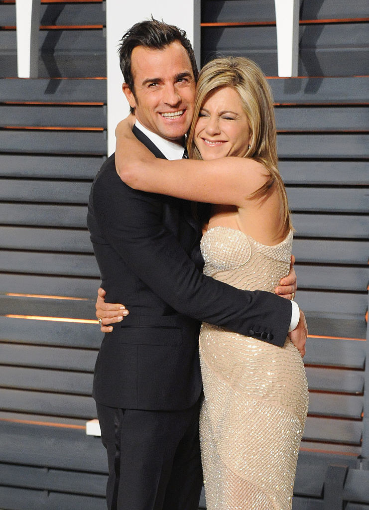 Justin Theroux (L) and Jennifer Aniston hugging at the 2015 Vanity Fair Oscar Party
