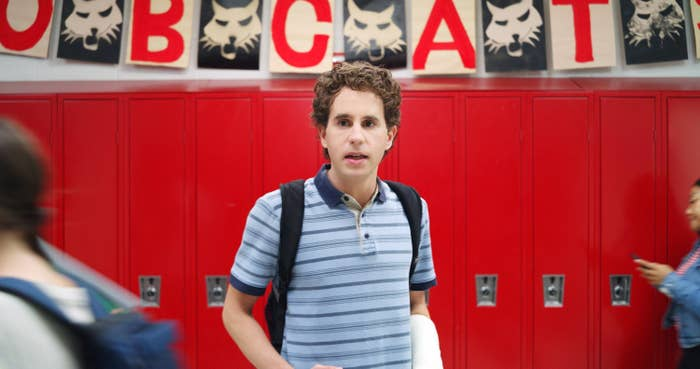 Evan Hansen walking through his high school hallway with a cast on his left arm