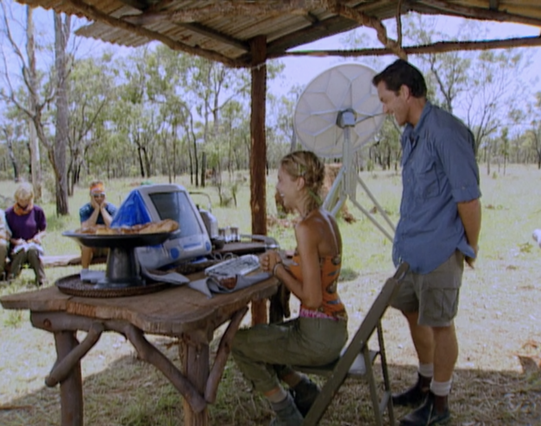 Elisabeth sits down at an iMac computer while Jeff stands behind her