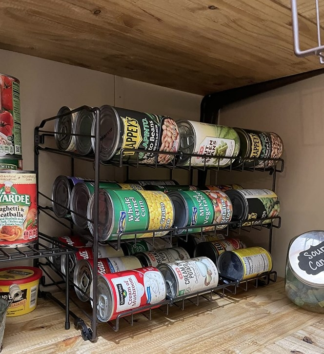 A reviewer displaying their black can rack organizer filled with cans of food on the kitchen counter