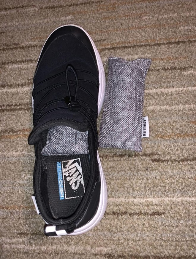 A reviewer displaying a charcoal deodorizer bag in their shoe