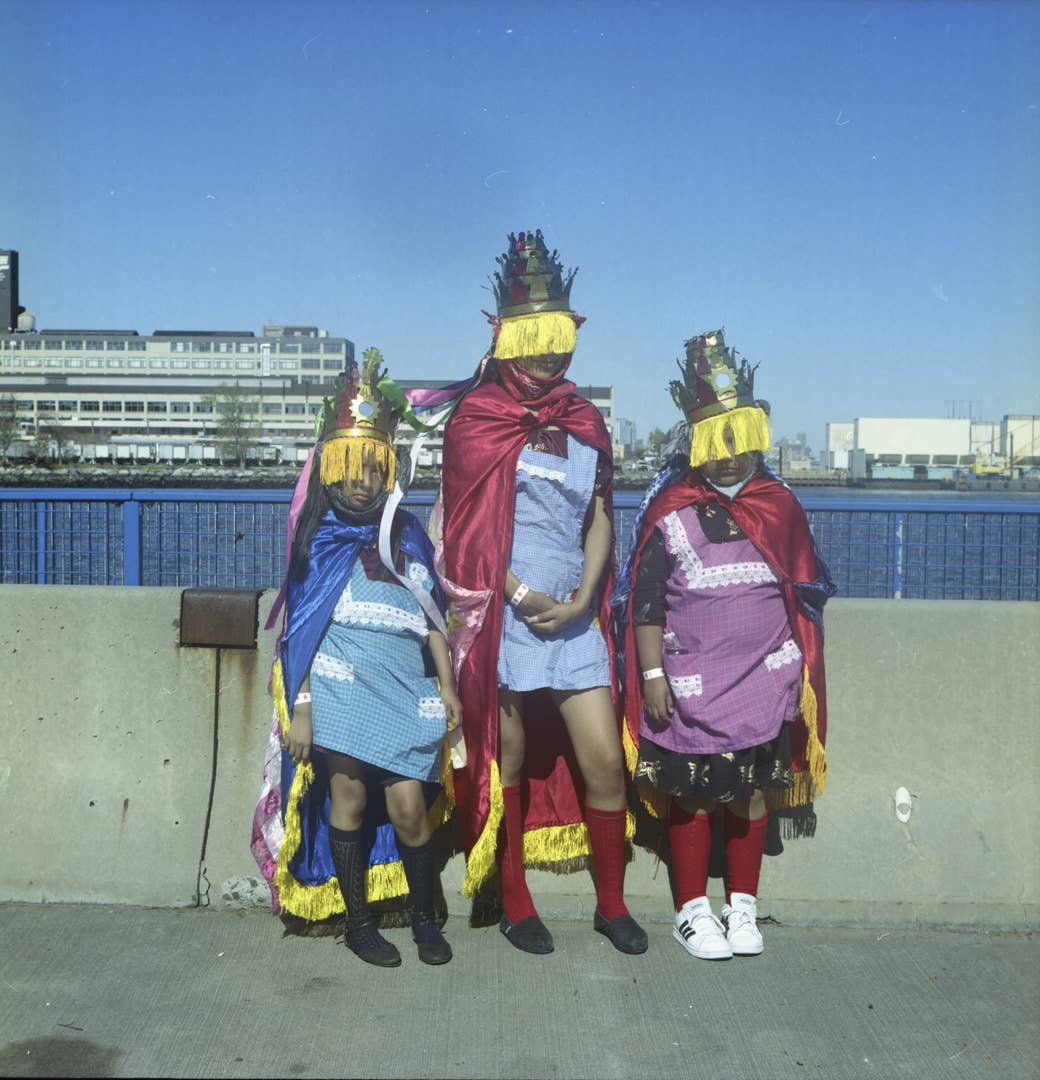Three women in Indigenous garb standing in front of a river in NYC
