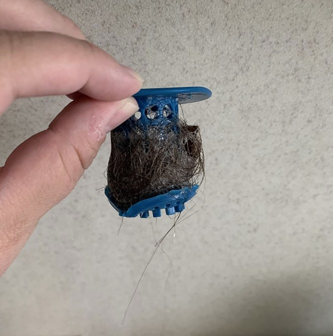 A reviewer holding up a TubShroom filled with hair from the drain