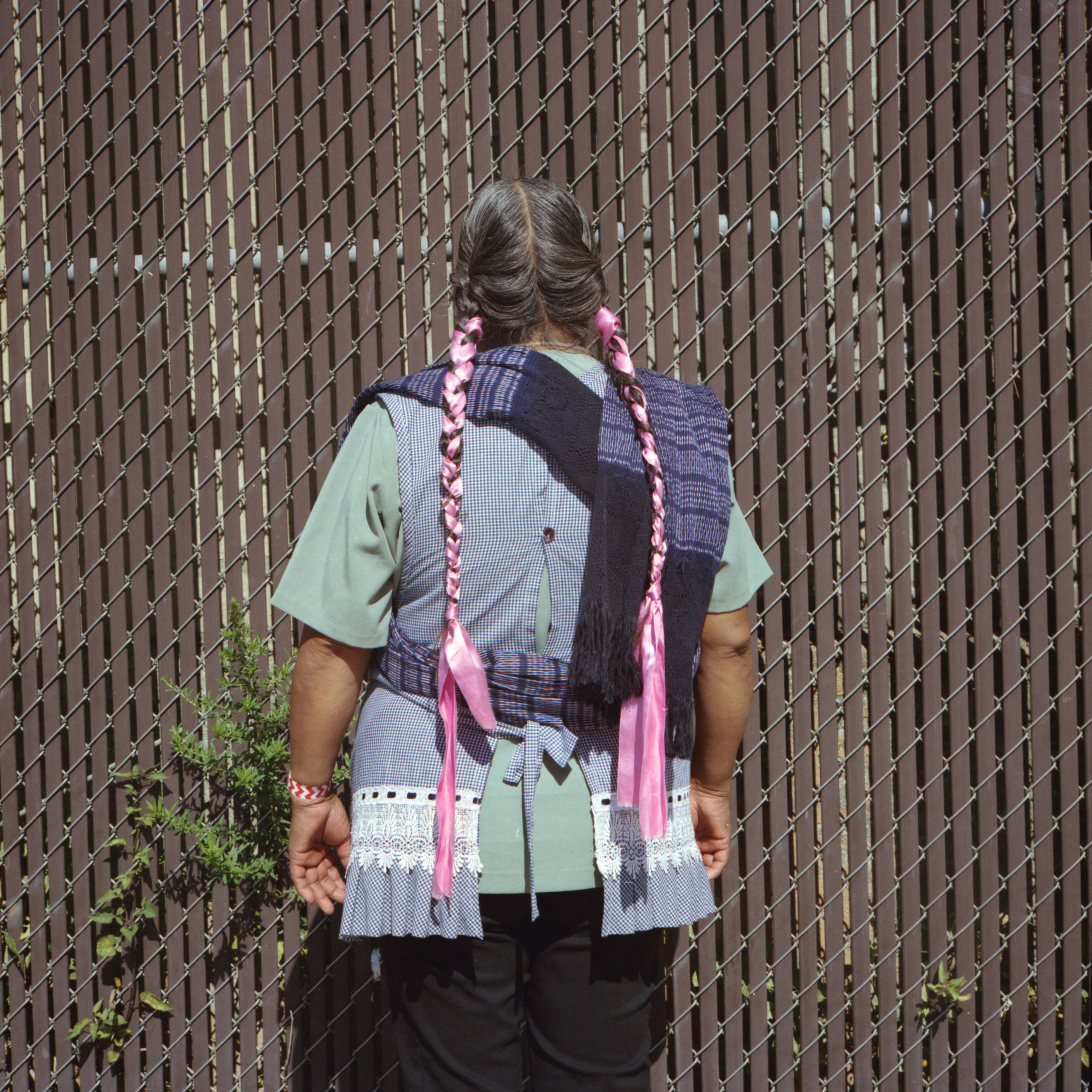 A woman photographed from behind with long braids and ribbons in her braids