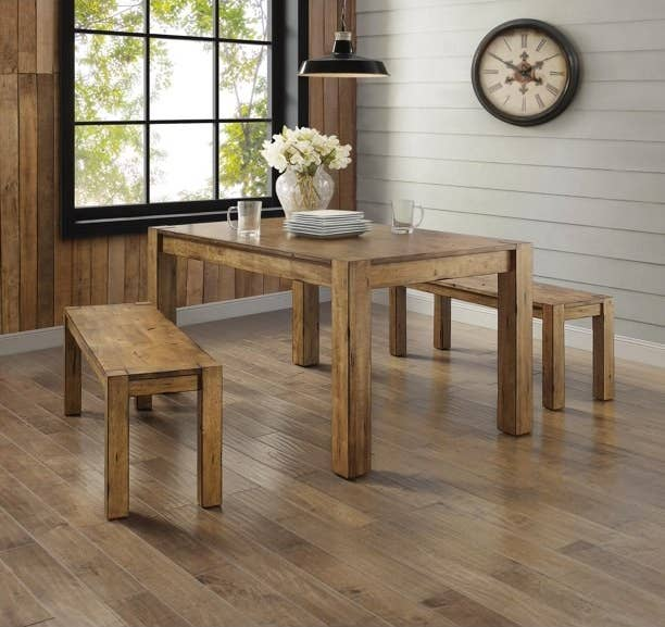 """Dining table shown in color """"Rustic Brown"""", with two dining benches, dishes and a vase with flowers on top."""