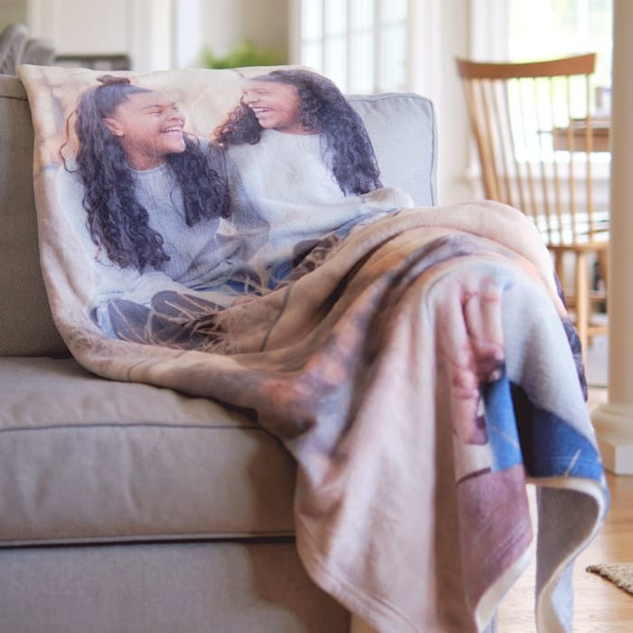 a large blanket draped across a couch with a photo of two models who look like they could be siblings