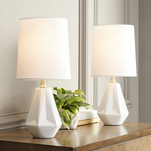 Two white lamps on a wood console with a potted plant in between them.